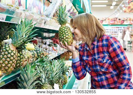 Woman Sniffing Pineapple In Store