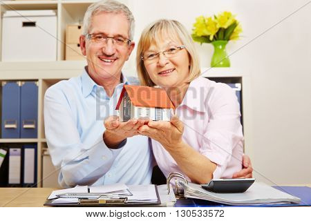 Old smiling senior couple holding a small house in their hands