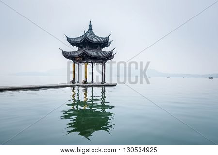 ancient pavilion on hangzhou west lake in mist rain China