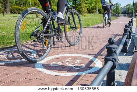 two bicyclists riding on the bike path outside on spring day