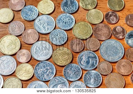 Different country coins on a wooden background