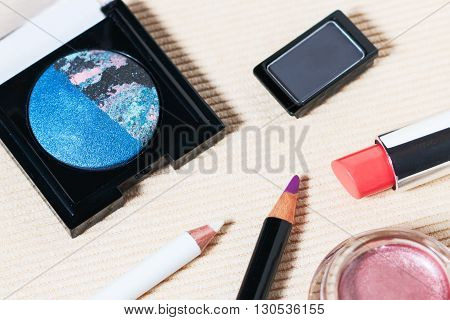 Makeup set of navy blue and rose pink eyeshadows, white and violet eye pencils and coral lipstick