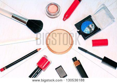 Set of makeup items of beige powder, black mascara, navy blue and rose eyeshadows, eyeliner, lip pencil, coral lipstick and nail polish