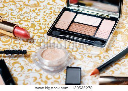 Makeup set of powder, natural makeup eyeshadows, mascara, red shiny lipstick and lip pencil