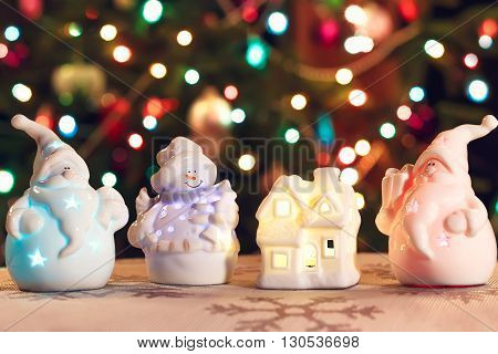 Illuminated Snowman, Christmas house and Jack Frost (Santa Claus) toys in front of Christmas tree lights that are defocused, blurred background