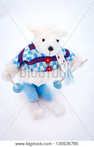 Fluffy cute soft white toy sheep skiing