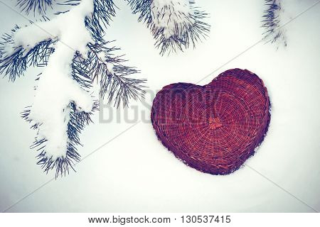 A rattan heart on snow background under pine tree branch, vintage effect