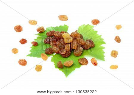 Dried raisins scattered on the leaf.Isolated on white background.