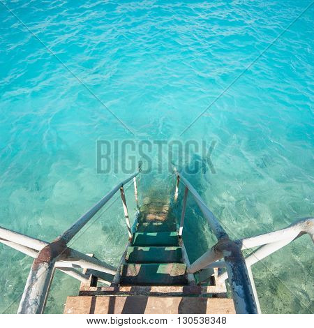 Old vintage metal wooden stairs leading to blue turquoise sea water from beach. Beautiful summer day. Swimming pool with grunge retro stairs on the ocean coast. Top View.