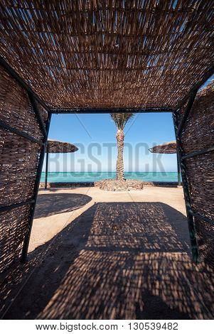 wicker sunshade shelter hovel on the beach in ocean sea resort. Vacation summer time.