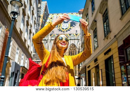 Young female tourist making selfie photo with Saint Stephen's cathedral in the center of Vienna