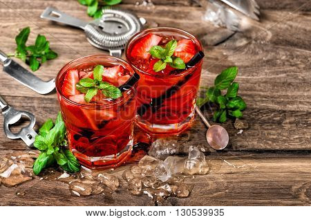 Red cocktail with ice mint leaves and strawberry. Alcoholic and non alcoholic drinks making bar tools