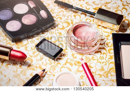 Makeup set of smokey eyes eyeshadow palette, brow powder, mascara, primer, eye pencils and lipsticks, selective focus