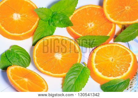 Cut orange fruit on a white plate with mint leaves