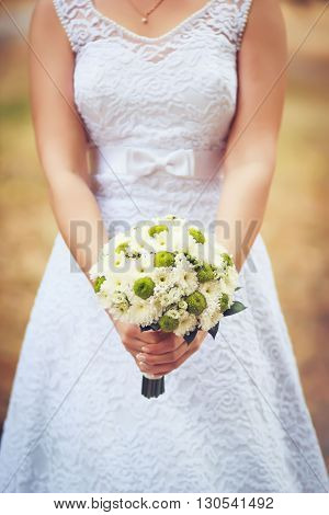 Bride holding bouquet of marguerites in her hands in a Wedding Day with blurry background