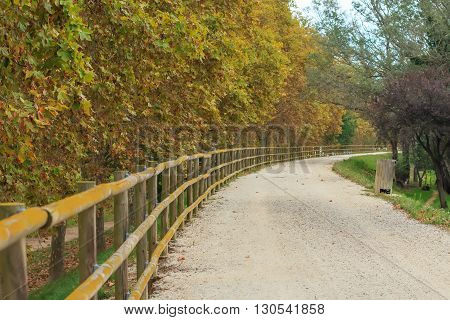 deserted gravel hiking path with wooden fence, defocused for background