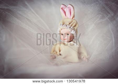 Ceramic doll newborn baby in veil closeup