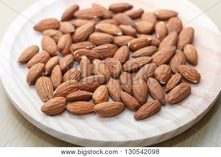Some almonds in a wooden bowl closeup