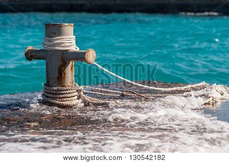 Rusty mooring bollard with ship ropes and  clear turquouse sea ocen water on background.