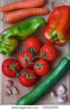 Fresh vegetables including tomatoes, zucchini, sweet green and red pepper, garlic, carrot on a wooden desk closeup, view from above