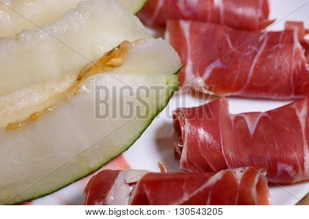 Closeup of slices of cured pork ham jamon with melon