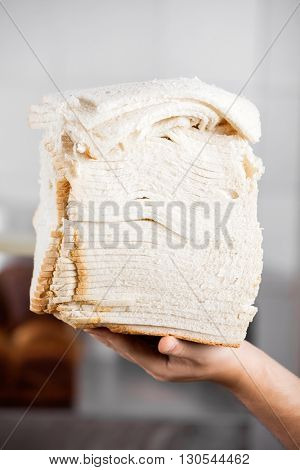 Baker's Hand Holding Stacked Bread Slices