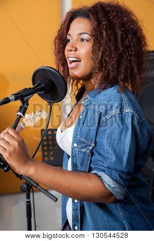 Female Band Member Singing In Recording Studio