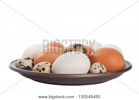 Quail and chicken eggs in a clay plate isolated on a white background