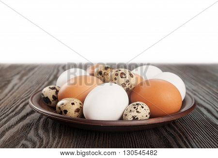 Quail and chicken eggs in a clay plate on a wooden table
