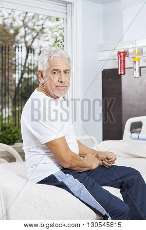 Confident Senior Man Sitting On Bed At Rehab Center