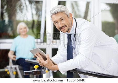 Confident Doctor Holding Digital Tablet While Leaning On Bar