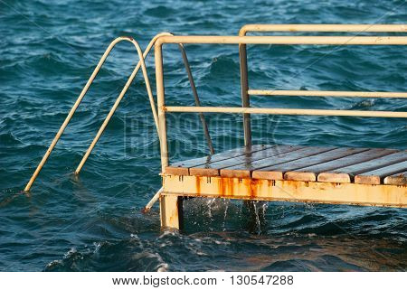 Old vintage metal wooden stairs leading to blue turquoise sea water from beach. Beautiful summer day. Swimming pool with grunge retro stairs on the ocean coast. Side View.