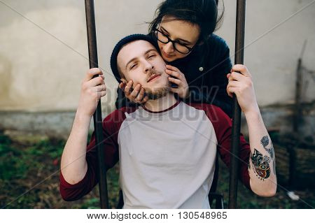 beautiful young couple posing on a swing