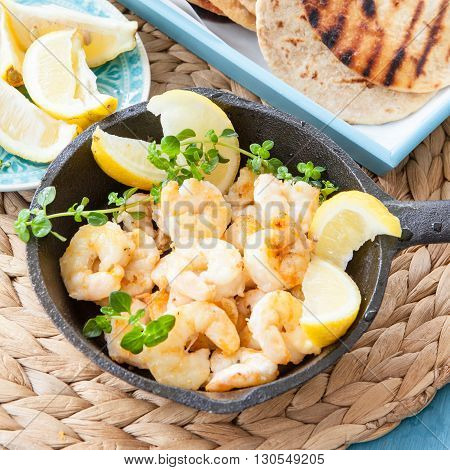Fried shrimps with fresh lemon and oregano in cast iron skillet