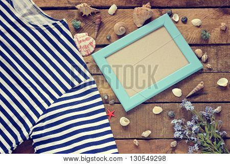 Marine still life top view. The concept of a holiday at sea. Shells photo frame vest and forget-me-not on a wooden platform.