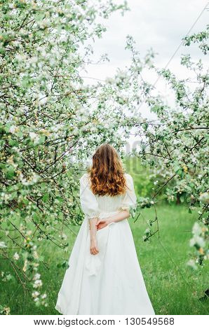 Young girl in a white dress and black hat in the in the white flowers garden. Woman in a beautiful long dress posing on a meadow in the fruit garden. Stunning bride in a wedding dress and red hair