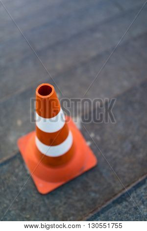 traffic cone, with white and orange stripes on gray staircace copy space.