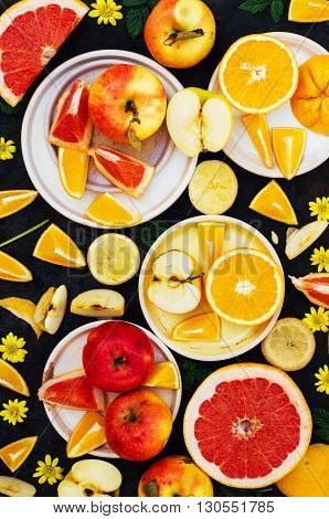 Mixed festive colorful tropical and citrus fruit sliced over black table top. Food collage on a rustic surface. Apples lemons grapefruit oranges berries. Citrus fruits background.