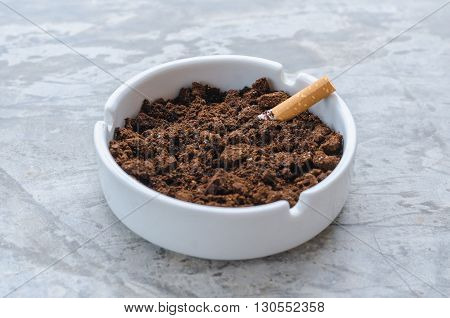 The ceramic ashtray contain coffee ground on concrete floor for protection fire from cigarette.