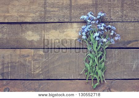 A small bouquet of forget-me-nots on a wooden platform top view.