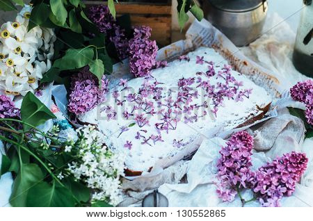 Homemade delicious fresh vanilla cake with apples sprinkled with powdered sugar and decorated with flowers and branches of lilac on a white kitchen table. Dessert cake for a large family. sweets