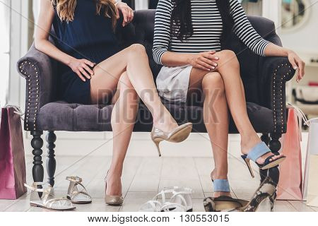 Confident with their choice. Part of young women with perfect legs keeping their legs crossed at knee while sitting on sofa at the shoe store