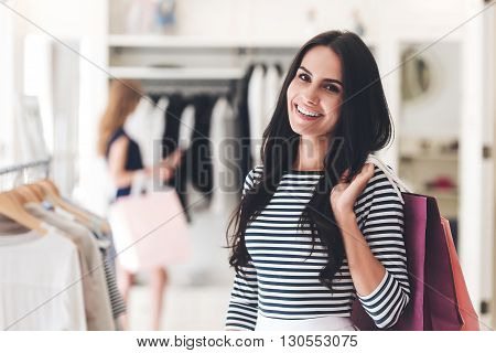 Shopping is her passion. Portrait of beautiful young woman with shopping bags looking at camera with smile while standing at the clothing store