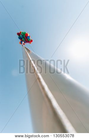 many bright baloons in the blue  sky on the pillar