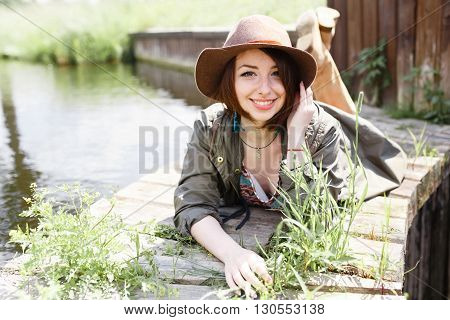 Bright stylish lifestyle portrait of pretty girl posing at hat. Outdoor vacation. Posing on wooden berth