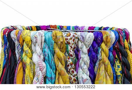 Colorful scarves on sale and hanging on stand.