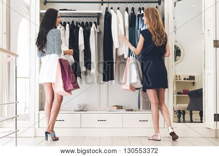 Shopping therapy with friend. Rear view of two beautiful women with shopping bags looking at each other with smile and picking clothing while standing at the store