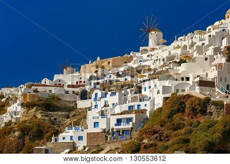 Windmills and white houses in Oia or Ia on the island Santorini, Greece
