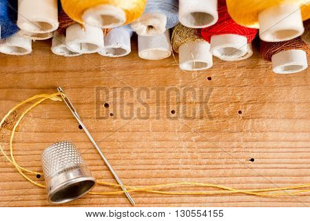 needle with thread and thimble o the wooden desk