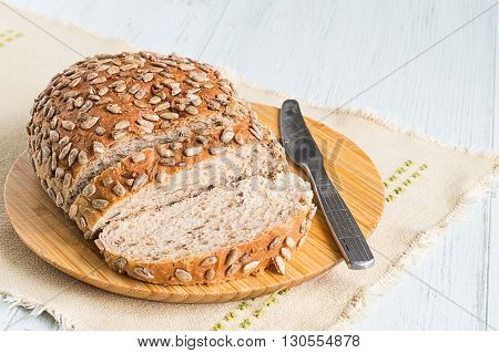Rye bread with cereals on a cutting board on a light wooden background.